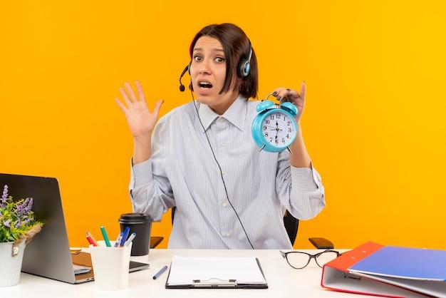 Ansiosa giovane ragazza della call center che indossa la cuffia avricolare che si siede allo scrittorio che tiene sveglia e che mostra la mano vuota isolata sull'arancio