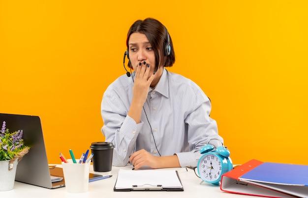 Ansioso giovane ragazza della call center che indossa la cuffia avricolare che si siede allo scrittorio che esamina il lato con la mano sulla bocca isolata sull'arancio