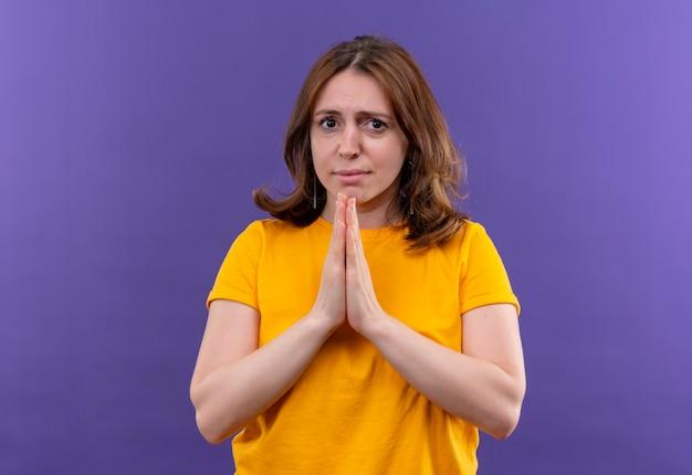 Обеспокоенная молодая случайная женщина, сложив руки в жесте молитвы на изолированном фиолетовом пространстве с копией пространства