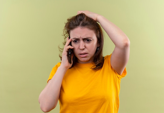 コピースペースと孤立した緑のスペースに頭を抱えて電話で話している気になる若いカジュアルな女性