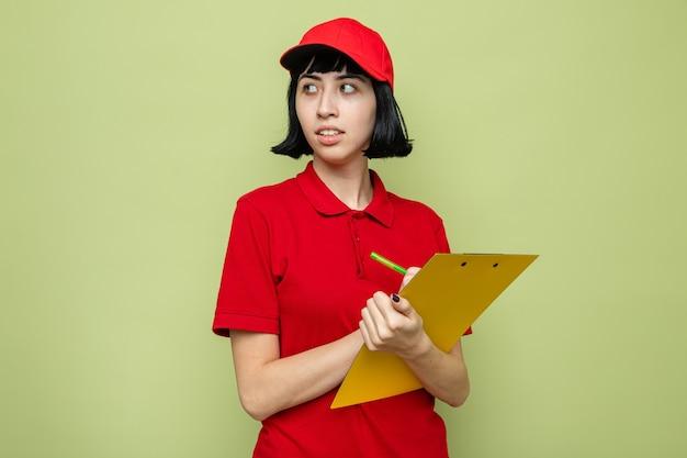 Giovane ragazza caucasica ansiosa delle consegne che tiene appunti e penna guardando a lato