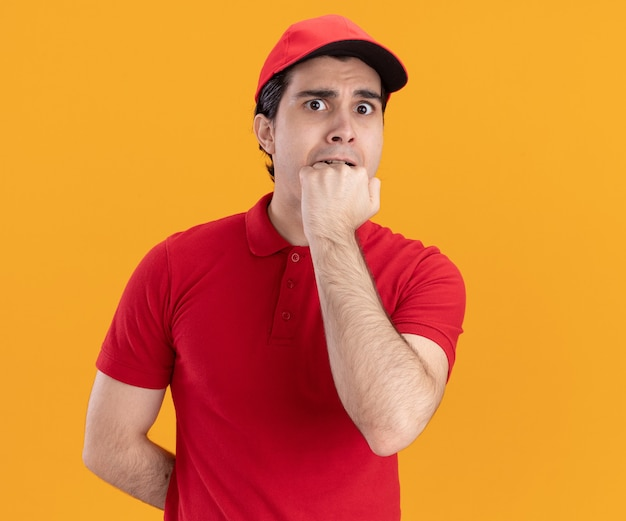 Anxious young caucasian delivery man in blue uniform and cap keeping hand behind back and another one on mouth