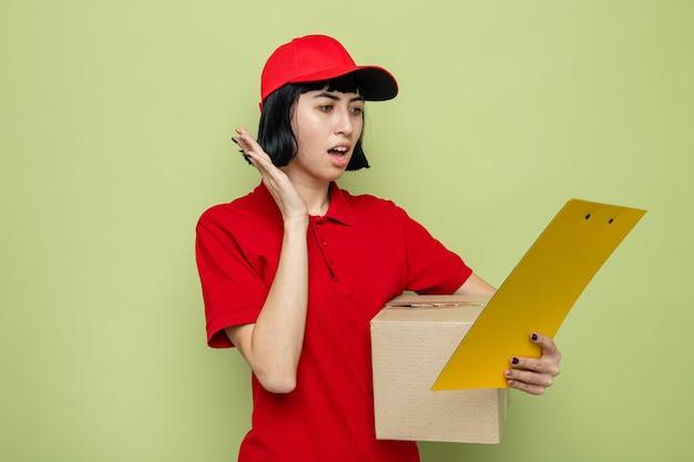 Ansiosa giovane donna di consegna caucasica che tiene in mano una scatola di cartone e guarda gli appunti