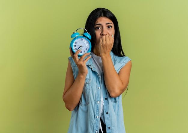 気になる若い白人の女の子は彼女の指を噛み、コピースペースでオリーブグリーンの背景に分離された目覚まし時計を保持します。