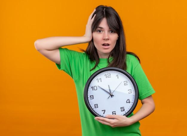 Ansiosa giovane ragazza caucasica in camicia verde tiene l'orologio e mise la mano sulla testa su sfondo arancione isolato