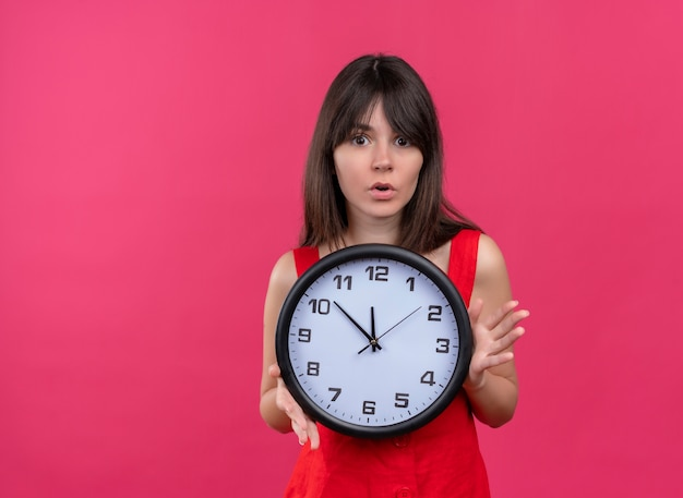Anxious young caucasian girl holding clock with both hands and looking at camera on isolated pink background with copy space