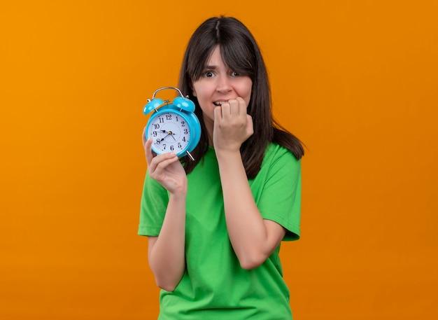 녹색 셔츠에 불안 젊은 백인 여자 시계를 보유하고 격리 된 오렌지 배경에 입에 손을 넣습니다