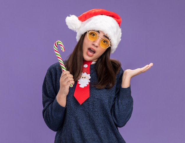 Встревоженная молодая кавказская девушка в солнцезащитных очках с санта-шляпой и санта-галстуком держит конфету и держит руку открытой изолированной на фиолетовом фоне с копией пространства