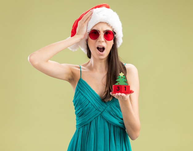 Ansiosa giovane ragazza caucasica in occhiali da sole con cappello santa mette la mano sulla testa e tiene l'ornamento dell'albero di natale