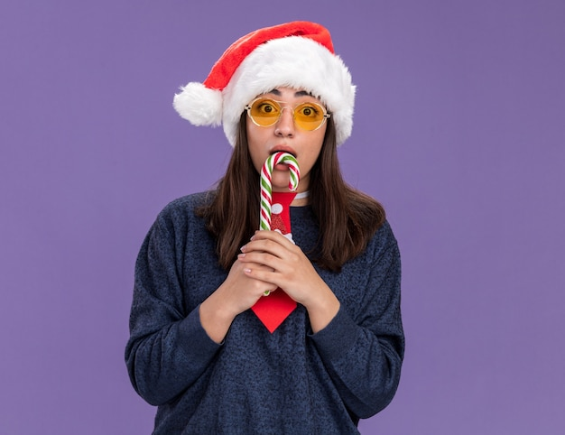 Anxious young caucasian girl in sun glasses with santa hat and santa tie holds candy cane isolated on purple wall with copy space