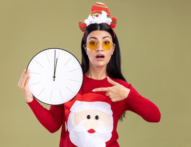 Ansiosa giovane ragazza caucasica che indossa la fascia di babbo natale e maglione con gli occhiali che tengono e che indica l'orologio isolato sulla parete verde oliva