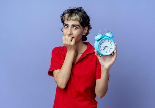 Тревожная молодая кавказская девушка со стрижкой пикси держит будильник и кусает пальцы на фиолетовом фоне с копией пространства