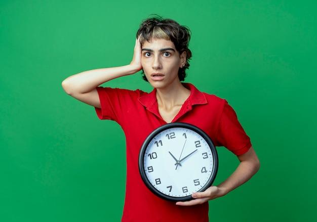 Ansiosa giovane ragazza caucasica con pixie haircut holding clock mettendo la mano sulla testa isolata su sfondo verde