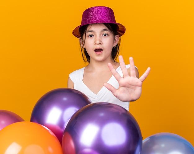 Встревоженная молодая кавказская девушка с фиолетовой шляпой жестикулирует знак стоп рука, стоящая с гелиевыми шарами, изолированными на оранжевой стене с копией пространства