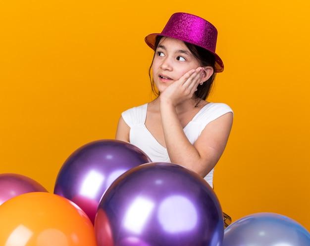 顔に手を置き、コピースペースとオレンジ色の壁に分離されたヘリウム気球で立っている側を見て紫色のパーティハットを持つ気になる若い白人の女の子