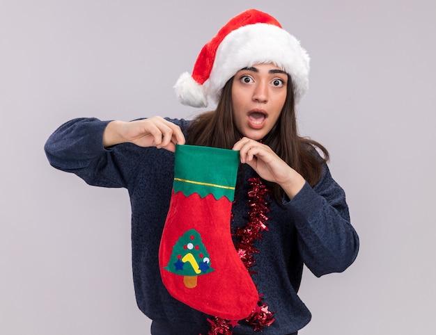 首の周りにサンタの帽子と花輪を持つ気になる若い白人の女の子は、クリスマスの靴下を保持します