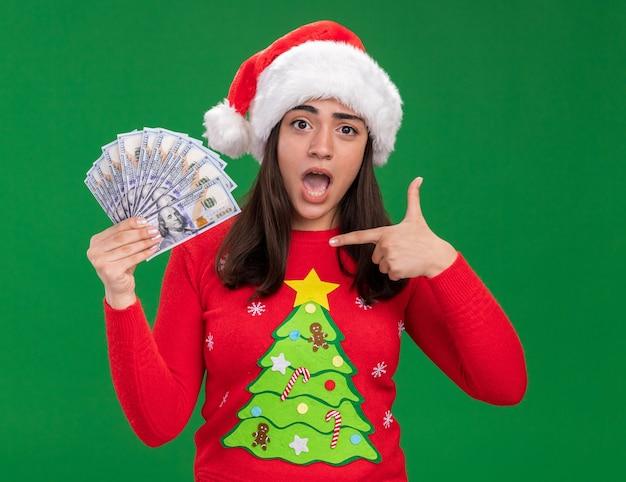 サンタの帽子をかぶって、コピースペースで緑の背景に分離されたお金を指差して気になる若い白人の女の子