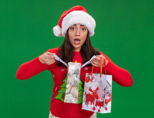 Взволнованная молодая кавказская девушка в шляпе санта-клауса держит бумажные подарочные пакеты, изолированные на зеленом фоне с копией пространства