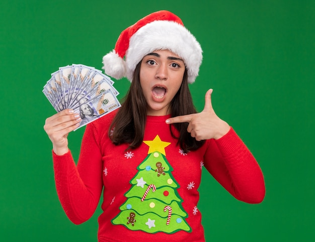 Anxious young caucasian girl with santa hat holds and points at money isolated on green background with copy space