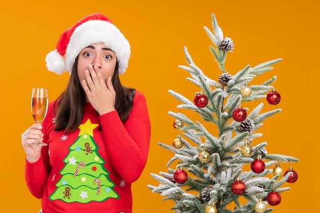산타 모자와 불안 젊은 백인 여자 입에 손을 넣고 복사 공간이 오렌지 배경에 고립 된 크리스마스 트리 옆에 서있는 샴페인 잔을 보유