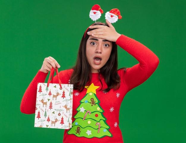 サンタのヘッドバンドを持つ気になる若い白人の女の子は額に手を置き、コピースペースで緑の背景に分離された紙のギフトバッグを保持します。
