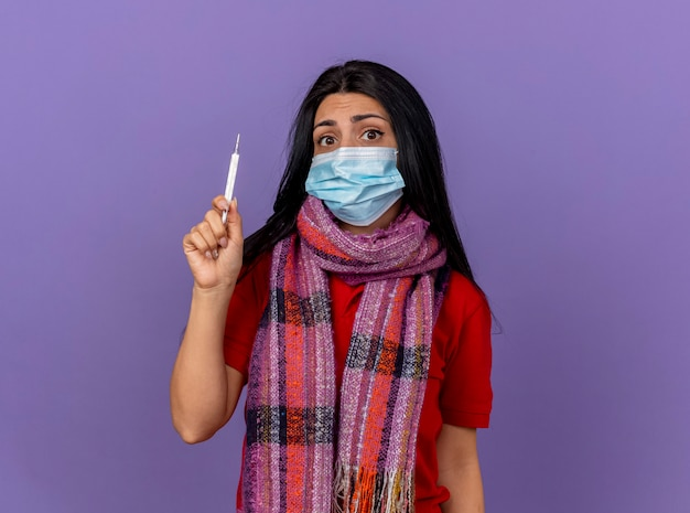 Тревожная молодая кавказская больная девушка в маске и шарфе держит термометр на фиолетовой стене с копией пространства