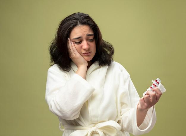 ナプキンとコピースペースでオリーブグリーンの背景に分離されたそれらを見て丸薬のパックを保持しているローブを身に着けている気になる若い白人の病気の女の子