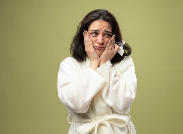 Ansioso giovane indoeuropeo ragazza malata che indossa accappatoio tenendo il tovagliolo e confezione di pillole guardando il lato mantenendo le mani sul viso isolato su sfondo verde oliva con spazio di copia