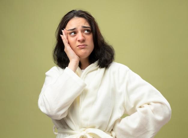 Тревожная молодая кавказская больная девушка в халате держит руку на талии, касаясь головы, глядя в сторону, изолированную на оливково-зеленом фоне