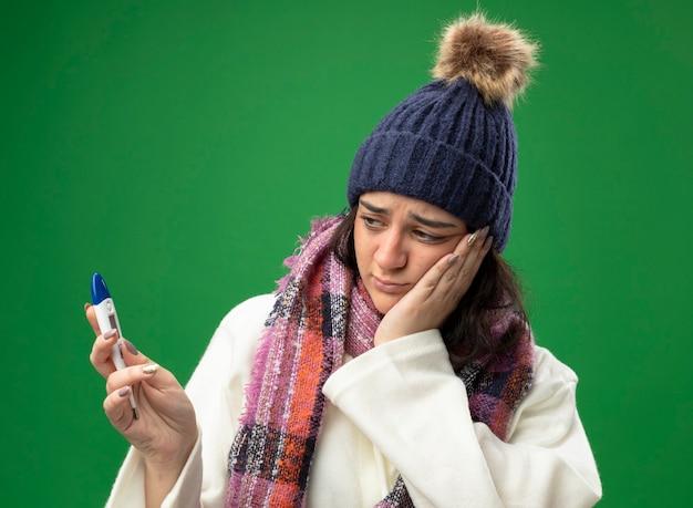 Ragazza malata caucasica giovane ansiosa che indossa il cappello e la sciarpa di inverno della veste che tengono e che esaminano il termometro che tiene la mano sulla faccia isolata sulla parete verde