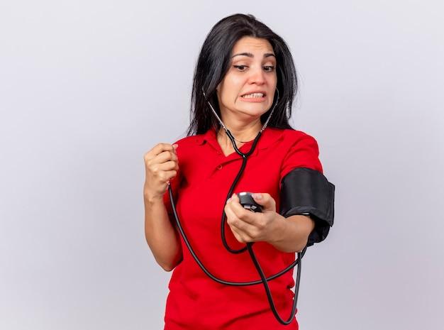 Тревожная молодая кавказская больная девушка со стетоскопом измеряет давление с помощью сфигмоманометра, глядя на него на белом фоне с копией пространства