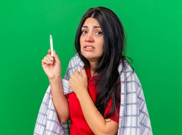 녹색 배경에 고립 된 카메라를보고 온도계를 들고 격자 무늬에 싸여 불안 젊은 백인 아픈 소녀
