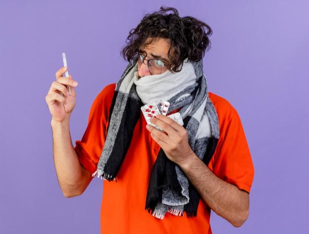 보라색 벽에 고립 된 온도계를보고 온도계와 의료 약을 들고 안경과 스카프를 착용하는 불안 젊은 백인 아픈 남자