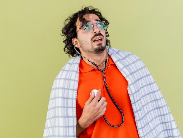Ansioso giovane uomo caucasico malato con gli occhiali e stetoscopio avvolto in un plaid ascoltando il proprio battito cardiaco cercando isolato sulla parete verde oliva con lo spazio della copia