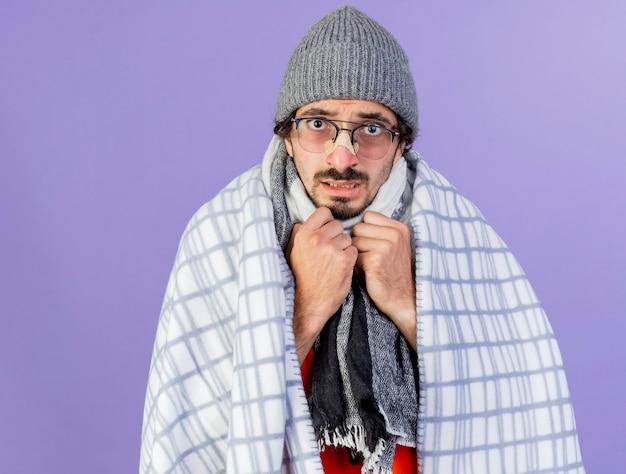 Ansioso giovane caucasico malato uomo con gli occhiali inverno cappello e sciarpa avvolti in plaid mantenendo le mani sul petto isolato sulla parete viola con spazio di copia