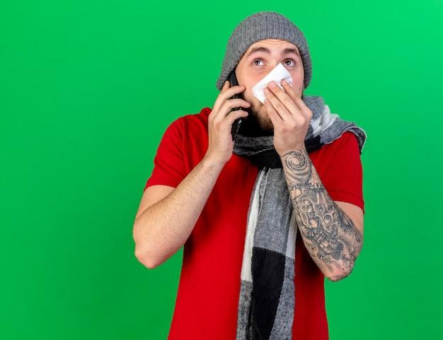 Ansioso giovane indoeuropeo uomo malato che indossa inverno cappello e sciarpa pulisce il naso con il tessuto parlando al telefono