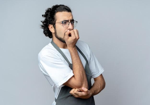 Ansioso giovane maschio caucasico barbiere con gli occhiali e fascia per capelli ondulati in uniforme mettendo la mano sul mento e un altro sul gomito guardando dritto isolato su sfondo bianco con spazio di copia