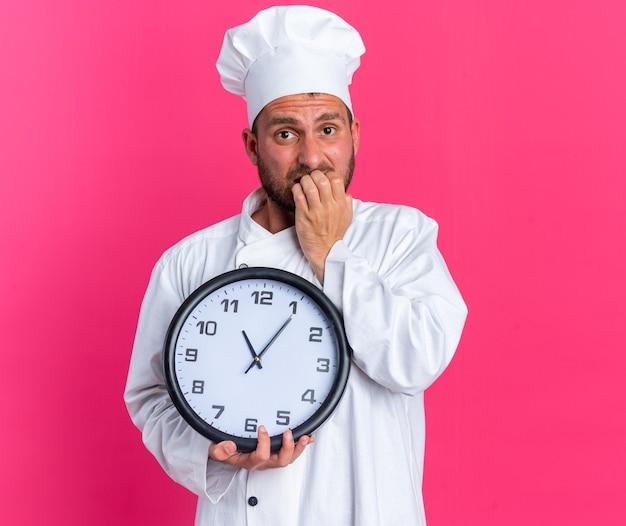 Ansioso giovane maschio caucasico cuoco in uniforme da chef e cappello che tiene l'orologio guardando la telecamera che morde le dita isolate sulla parete rosa
