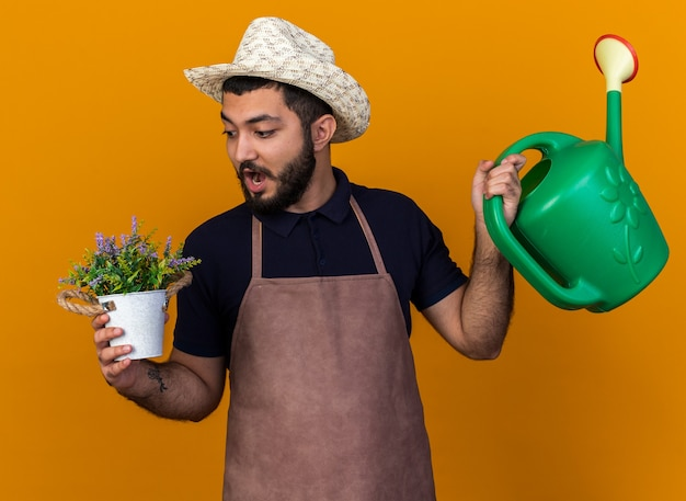 Anxious young caucasian male gardener wearing gardening hat holding watering can and looking at flowerpot isolated on orange wall with copy space