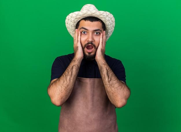 Встревоженный молодой кавказский садовник в садовой шляпе кладет руки на лицо, изолированное на зеленой стене с копией пространства