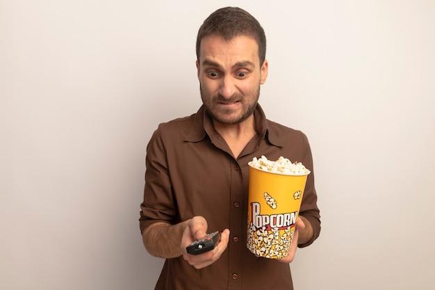 Ansioso giovane uomo caucasico tenendo la benna di popcorn e telecomando guardando il telecomando premendo il pulsante isolato su sfondo bianco con spazio di copia