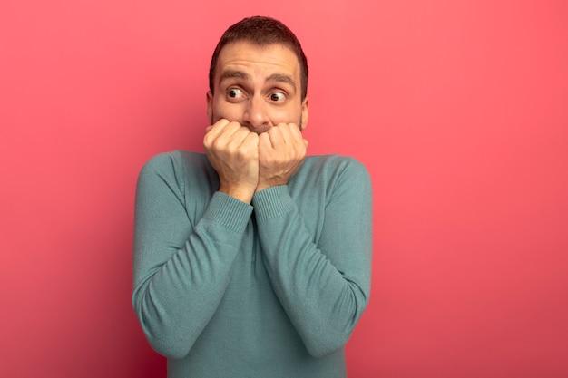 Ansioso giovane uomo caucasico mantenendo le mani sulla bocca guardando il lato isolato sulla parete cremisi con lo spazio della copia