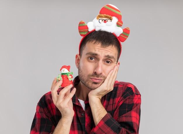 Тревожный молодой кавказский мужчина в повязке на голову санта-клауса, держащий снеговика, рождественское украшение, держа руку на лице, изолированном на белой стене