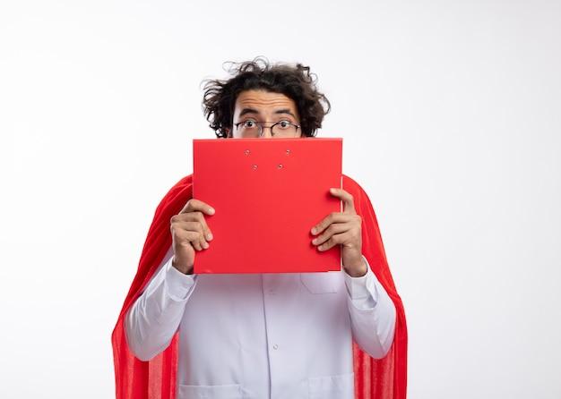 赤いマントと聴診器を首に巻いた医者の制服を着た光学眼鏡をかけた気になる若い白人のスーパーヒーローの男がファイルフォルダを保持して見ています
