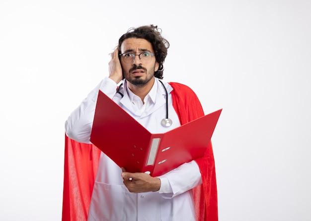 赤いマントと聴診器を首にかけた医者の制服を着た光学ガラスの気になる若い白人のスーパーヒーローの男は、頭に手を置き、白い壁に隔離されたファイルフォルダーを保持します