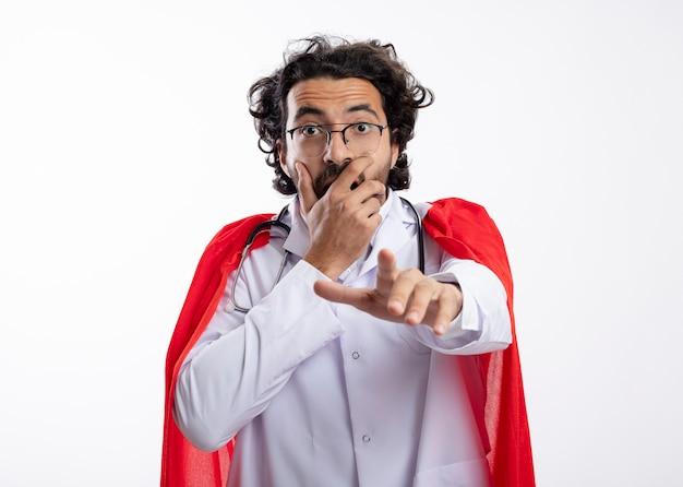 赤いマントと聴診器を首にかけた医者の制服を着た光学ガラスの気になる若い白人のスーパーヒーローの男は、口に手を置き、白い壁に隔離されたポイント