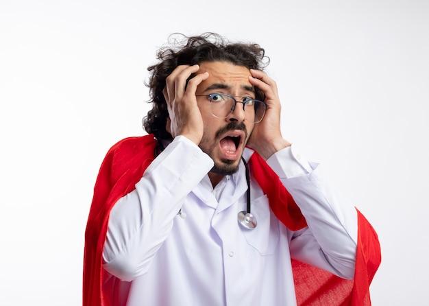 Ansioso giovane supereroe caucasico uomo in occhiali ottici che indossa l'uniforme del medico con mantello rosso e con lo stetoscopio intorno al collo mette le mani sul viso