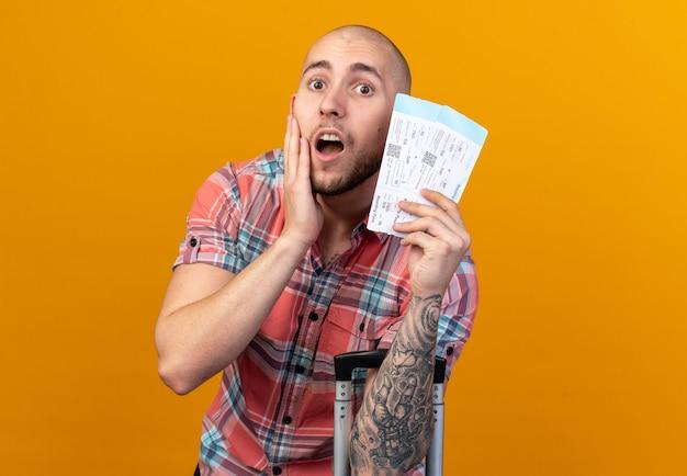 Ansioso giovane viaggiatore caucasico uomo con biglietti aerei e mettendo la mano sul viso isolato sulla parete arancione con spazio copia