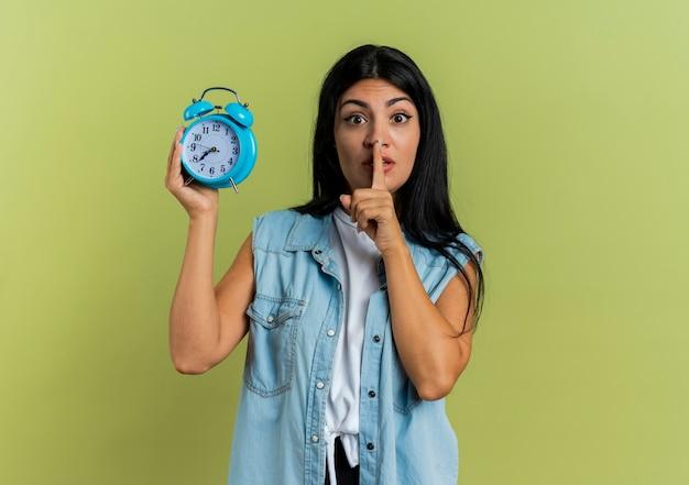 気になる若い白人女性は、沈黙のサインをジェスチャーし、コピースペースでオリーブグリーンの背景に分離された目覚まし時計を保持します。