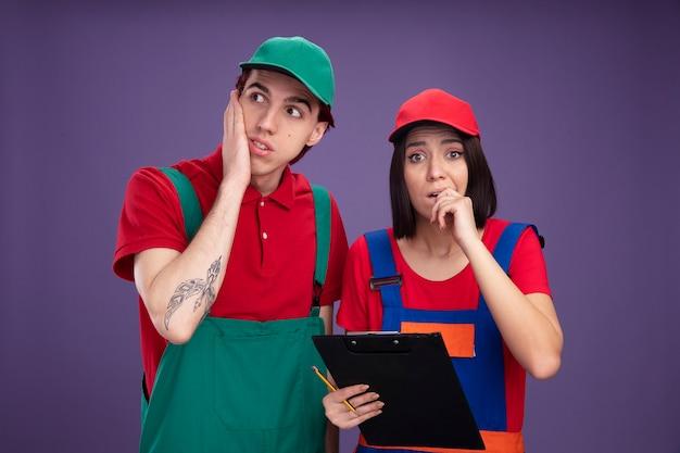 Ansiosa giovane coppia in uniforme da operaio edile e berretto ragazza che tiene matita e appunti mordere il dito guardando la telecamera ragazzo tenendo la mano sul viso guardando il lato isolato sul muro viola